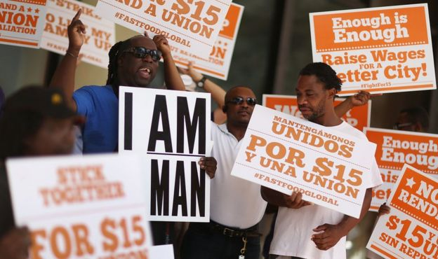 Protesters in support of a $15 an hour minimum wage stand together on September 10, 2015 in Fort Lauderdale, Florida.