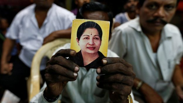 A supporter of Tamil Nadu Chief Minister Jayalalithaa Jayaraman holds her photo at the AIADMK party office in Mumbai, India, December 5