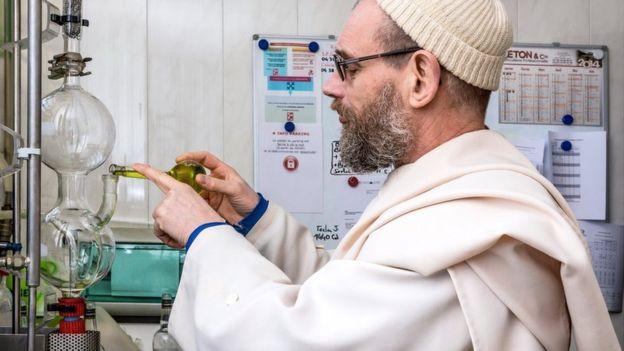 Monje revisando el proceso de destilación