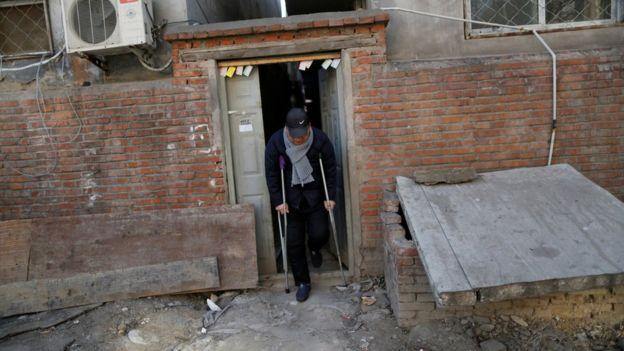 Hombre sale en muletas de una casa semiderruida de ladrillos rojos.