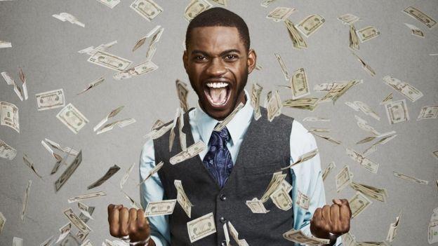 Homem debaixo de chuva de dinheiro