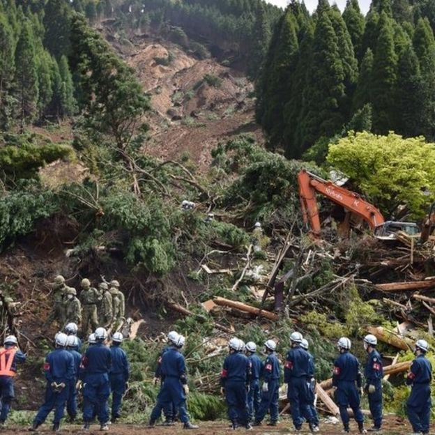 Soldiers and rescue workers examine a landslide site in the aftermath of two earthquakes in Minami-Aso, Kumamoto prefecture (17 April 2016)