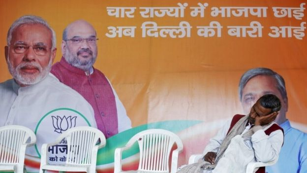 A worker of Bharatiya Janata Party (BJP) takes a nap in front of the party