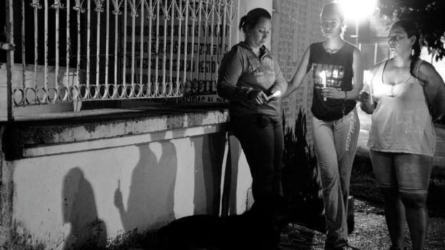 Mujeres con velas frente al cementerio.