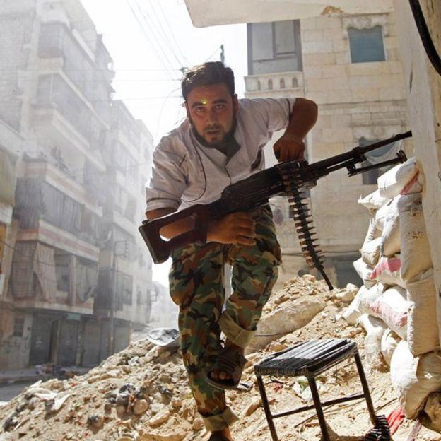 Un hombre armado corre en una destruida Alepo.