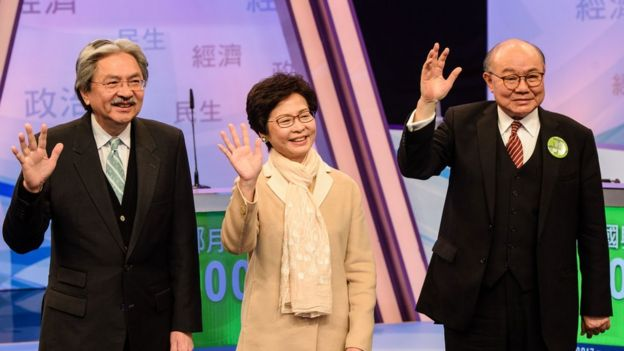 Hong Kong's three leadership candidates (L-R) John Tsang, Carrie Lam and ex-judge Woo Kwok-hing wave as they arrive at a studio before facing off in their first televised debate in Hong Kong on March 14, 2017.