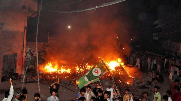 An angry mob after they set fire to household items belonging to a minority Ahmadi Muslim resident in the low-income Arafat Colony of the eastern city of Gujranwala, 27 July 2014