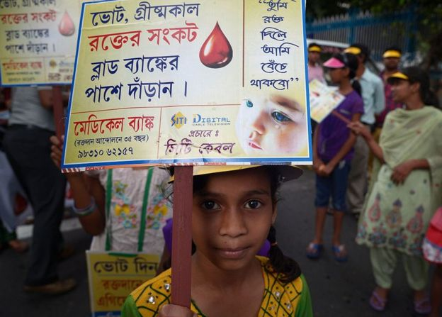 Indian children hold placards as they walk in a rally to promote blood donations in Kolkata on April 12, 2015