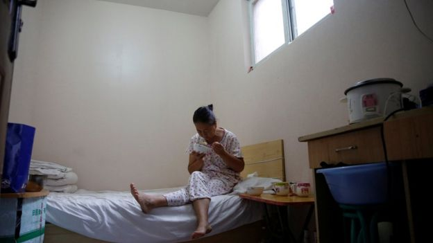 Mujer come sobre la cama. Se ve convaleciente.