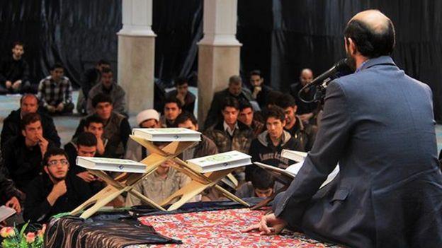 Man recites Koran in front of audience of young men