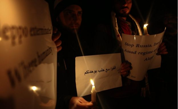 Activists hold banners during a candlelight gathering in solidarity with the people of Aleppo, in light of recent developments reported on the besieged city, in Douma, East Ghouta area, near Damascus,