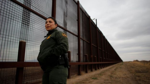US border patrol agent stands next to the border fence separating the United States and Mexico.