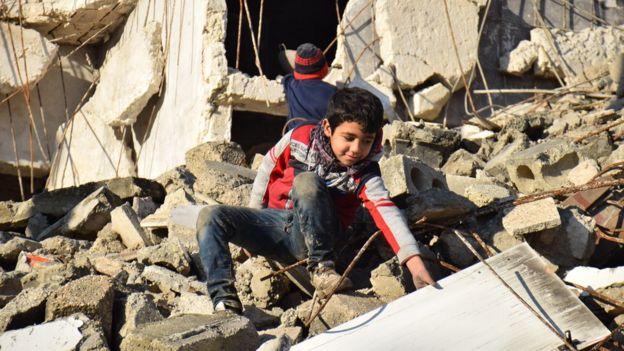 Doğu Halep'te çocuklar yıkılan binalarda oyunuyor