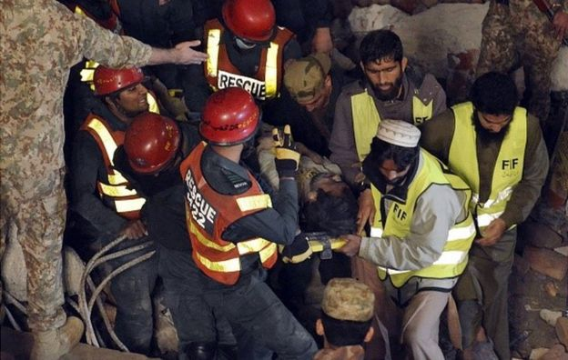 Pakistani rescuers remove a victim from the rubble of a collapsed factory on the outskirts of Lahore on November 4, 2015.