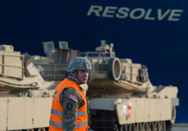 A US soldier walks in front of US Army tanks and the cargo vessel