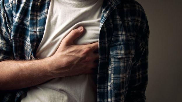 Hombre con la mano en el pecho.