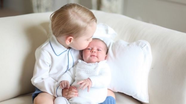 Prince George kisses his new baby sister Princess Charlotte.