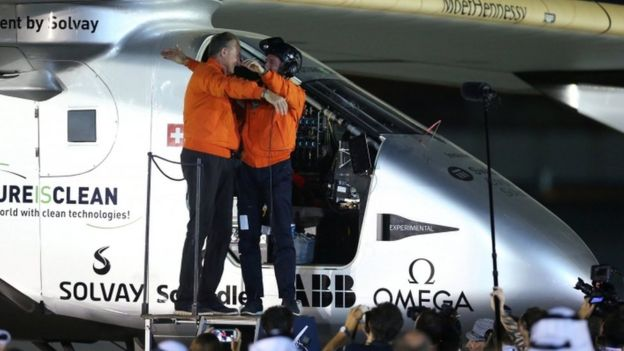Pilots Andre Borschberg (L) and Bertrand Piccard hug at the end of the Solar Impulse's round-the-world journey