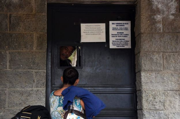 Un policía atiende a una mujer a la puerta del Hogar Seguro Virgen de la Asunción de Guatemala el 8 de marzo.