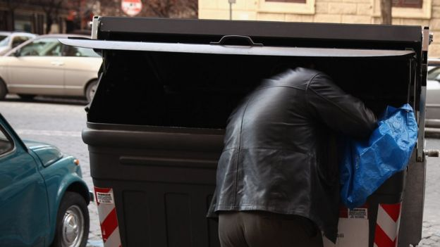 A man looks through a rubbish bin in Rome, Italy