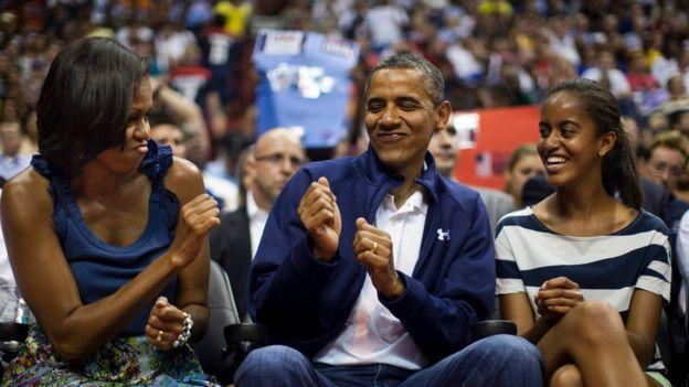 Obama con Michelle y una de sus hijas en un partido de básquetbol