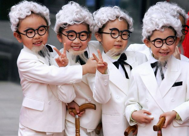 Chinese children dress up as Colonel Sanders at the opening of a KFC in Beijing, 2006