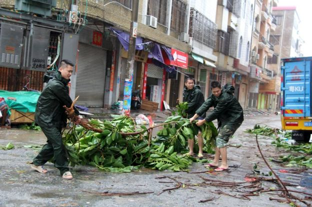 People try to remove a bough from a street as Typhoon Mujigae hits Maoming, Guangdong province, 4 October 2015