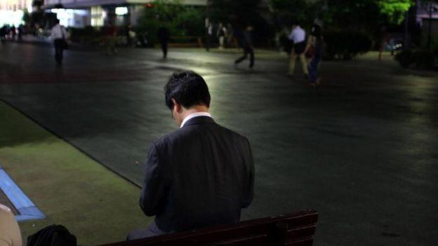 Un hombre sentado en un banco en la calle, de espaldas