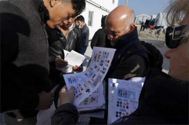 Migrants receive documents in Calais explaining removal process