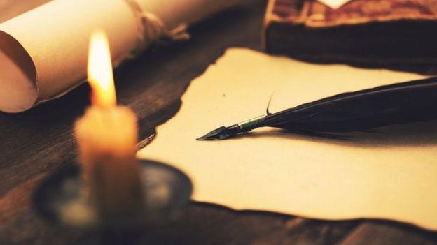 Rollos de papel, una pluma fuente y una vela