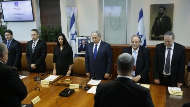 Israeli Prime Minister Benjamin Netanyahu, center, and his cabinet ministers observe a moment of silence during a special cabinet meeting to mourn the death of former Israeli President Shimon Peres, in Jerusalem, Wednesday, Sept. 28, 201