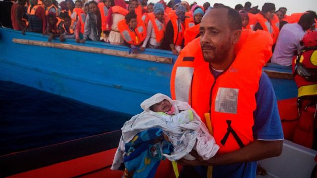 A man carries his five days old son after been rescued