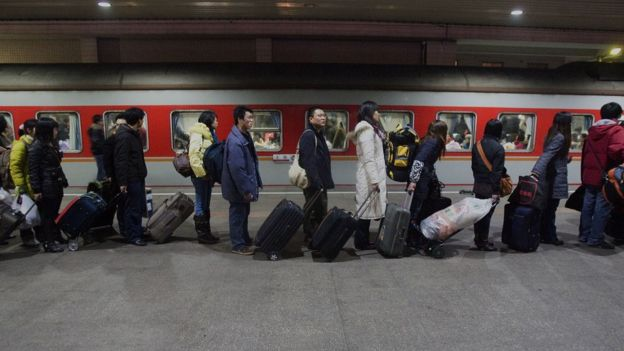 Passengers line up to board a train at the Shanghai Railway Station on January 21, 2009 in Shanghai, China