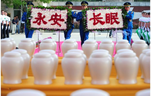 Attendants approach a table filled with biodegradable urns while carrying a floral display with characters meaning 'rest in peace forever' during a procession at a cemetery in Tianjin, northern China, for a collective eco-burial on 20 July 2010