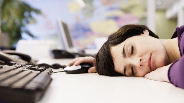 Mujer adormecida sobre el teclado de la computadora