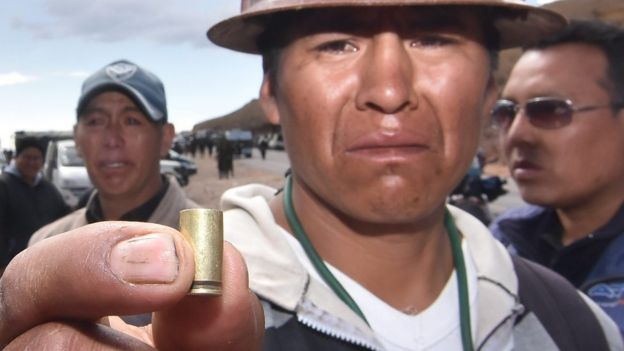 A Bolivian miner shows a bullet shell that was used to kill one of the two dead miners