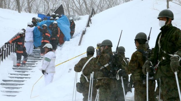 Firefighters carry a survivor they rescued from the site of an avalanche in Nasu town, Tochigi prefecture on 27 March 2017, while Self Defense Force personnel look on