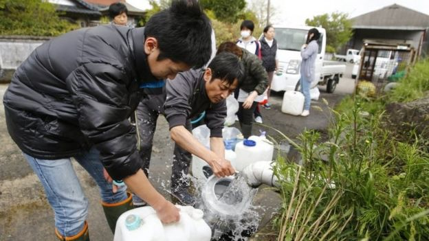 Evacuees collect spring water in plastic containers in Aso, Kumamoto prefecture, Japan (17 April 2016)