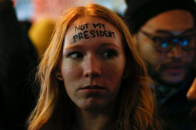 A woman looks on as she takes part in a protest against President-elect Donald Trump in front of Trump Tower in New York, 10 November
