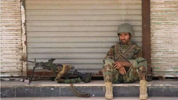 An Afghan National Army (ANA) soldier sits in front of a closed shop in the downtown of Kunduz city, Afghanistan October 3, 2016.