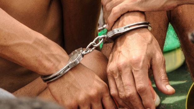 Dos presos esposados