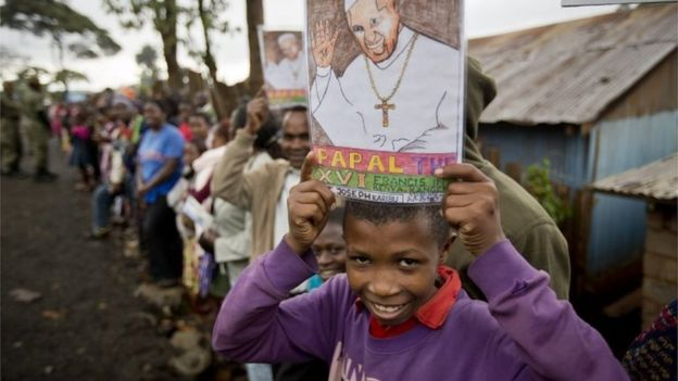 A boy holds a picture of Pope Francis as he awaits his arrival at the St Joseph The Worker Catholic Church in the Kangemi slum of Nairobi, Kenya