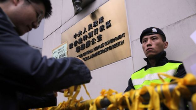 A man ties a yellow ribbon onto a barricade outside the residence of Beijing's representative in Hong Kong