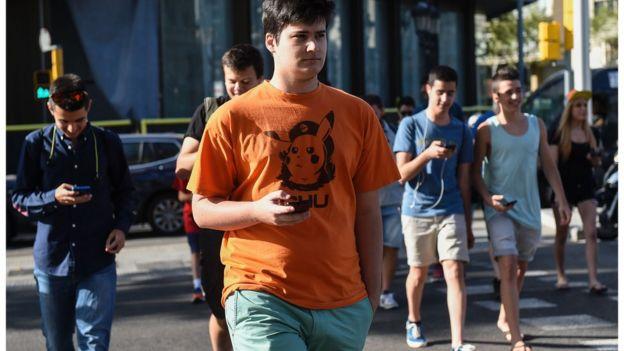 Jóvenes en la calle con teléfonos celulares