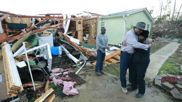 Two people hug near their home wrecked by a storm in the US