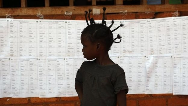 A child stands in front of a voters' list at a polling station in Bangui (14 February 2016)