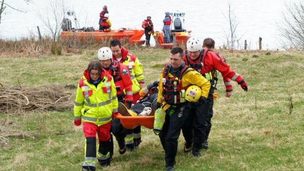 Emergency response volunteers carrying a man on a stretcher