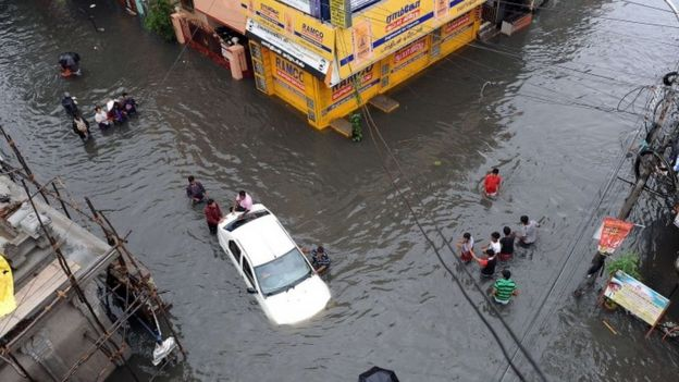 Indian residents attempt to push a vehicle through floodwaters as others wade past in Chennai on December 2, 2015.