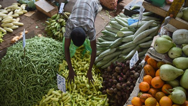 A Sri Lankan stallholder arranges vegetables at a market in Colombo
