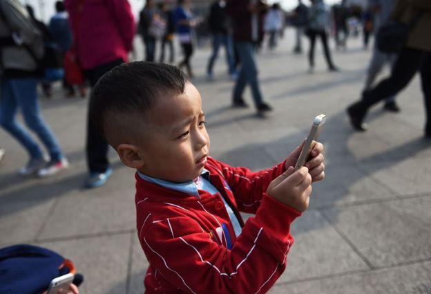 Iphone'uyla fotoğraf çeken bir çocuk